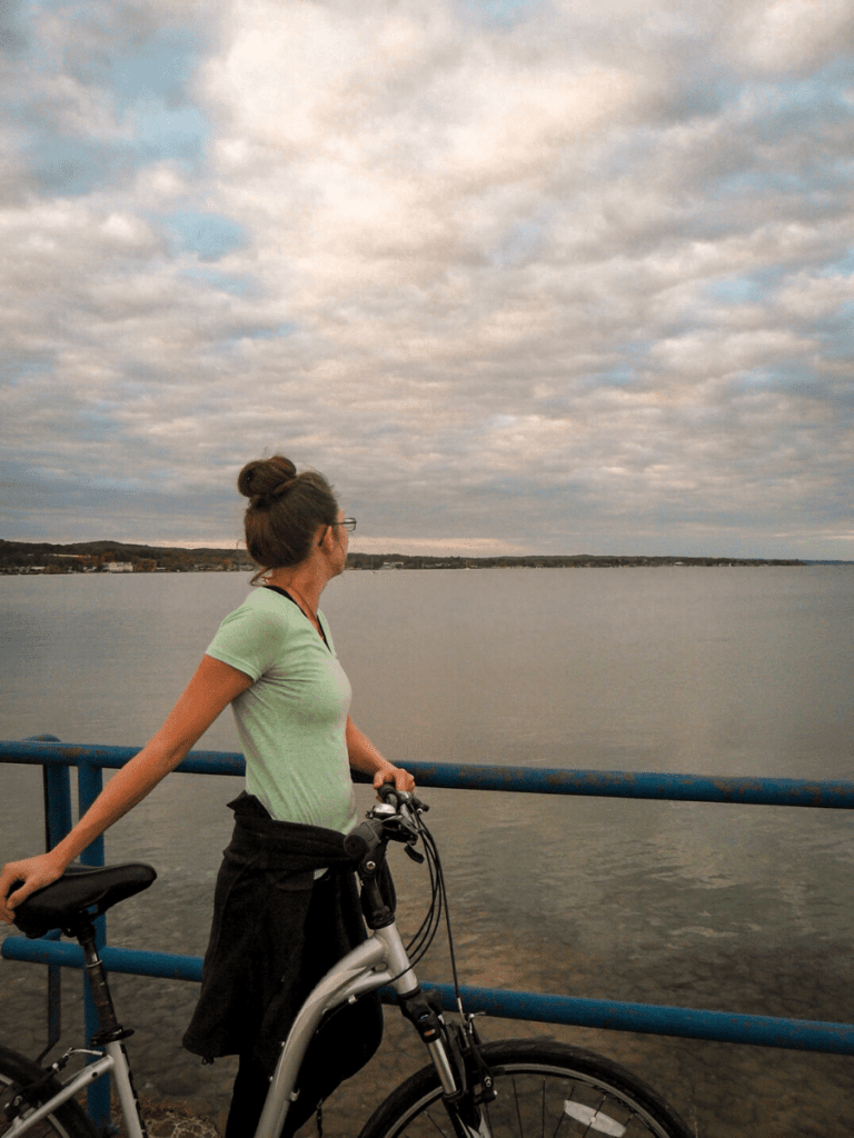 Girl standing next to bike looking out at lake- activities in traverse city