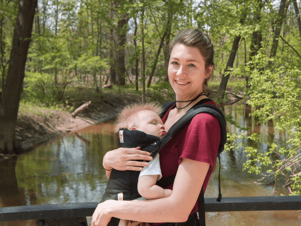 Mom wearing sleeping boy in baby carrier-outdoor gear for babies