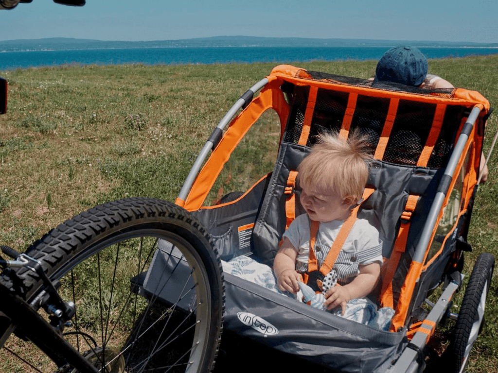 small boy sitting in bike trailer- outdoor gear for babies
