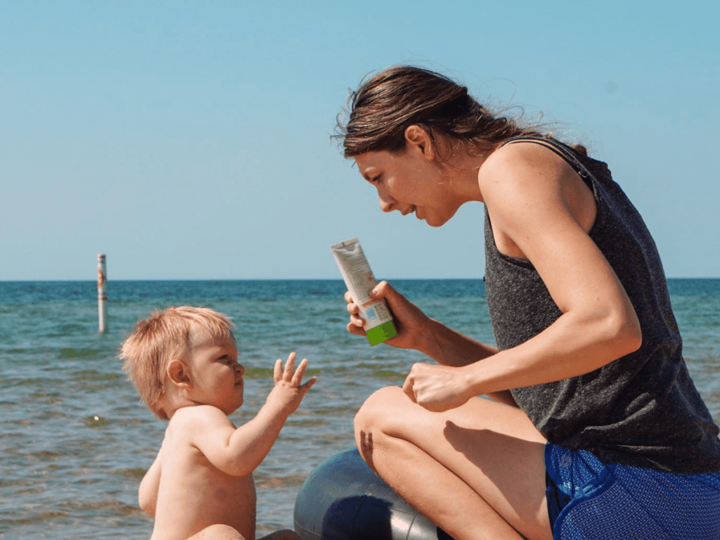 small boy and mom sitting on beach while mom holds up sunscreen- outdoor gear for babies