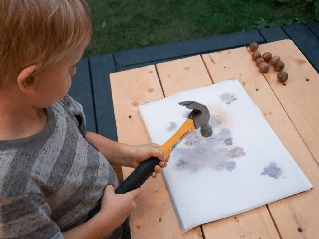small boy pounding flowers onto paper with hammer- flower crafts