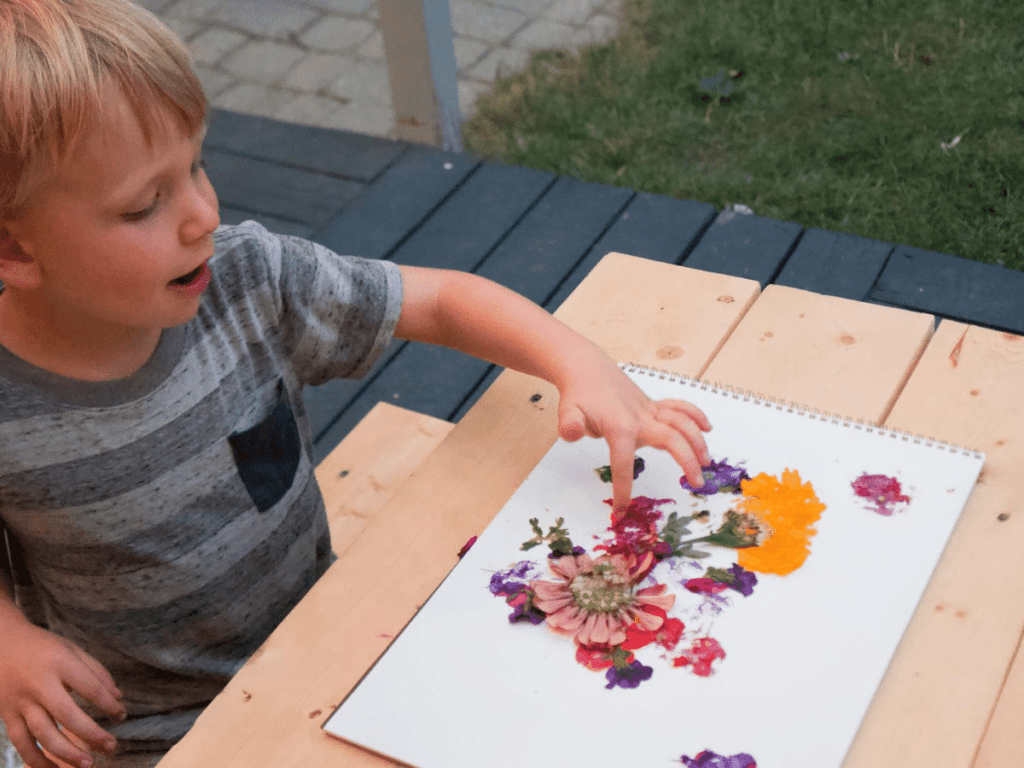 small boy pointing at crushed flowers on paper- flower crafts