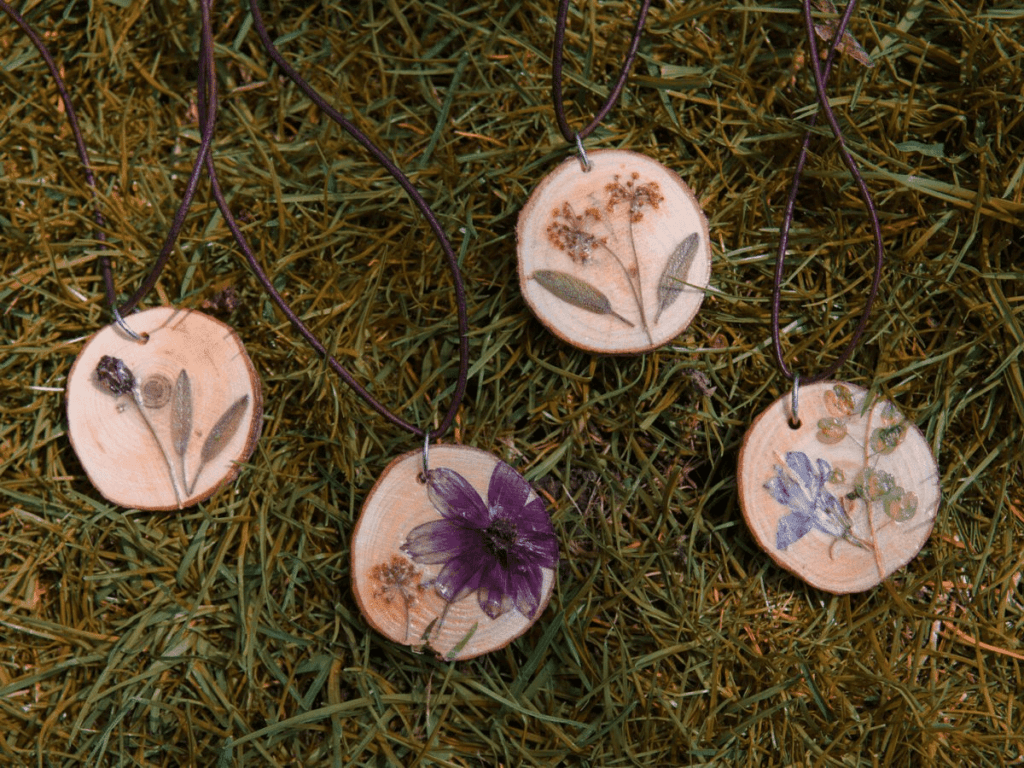 close up of wood slice necklaces with pressed flowers- flower crafts