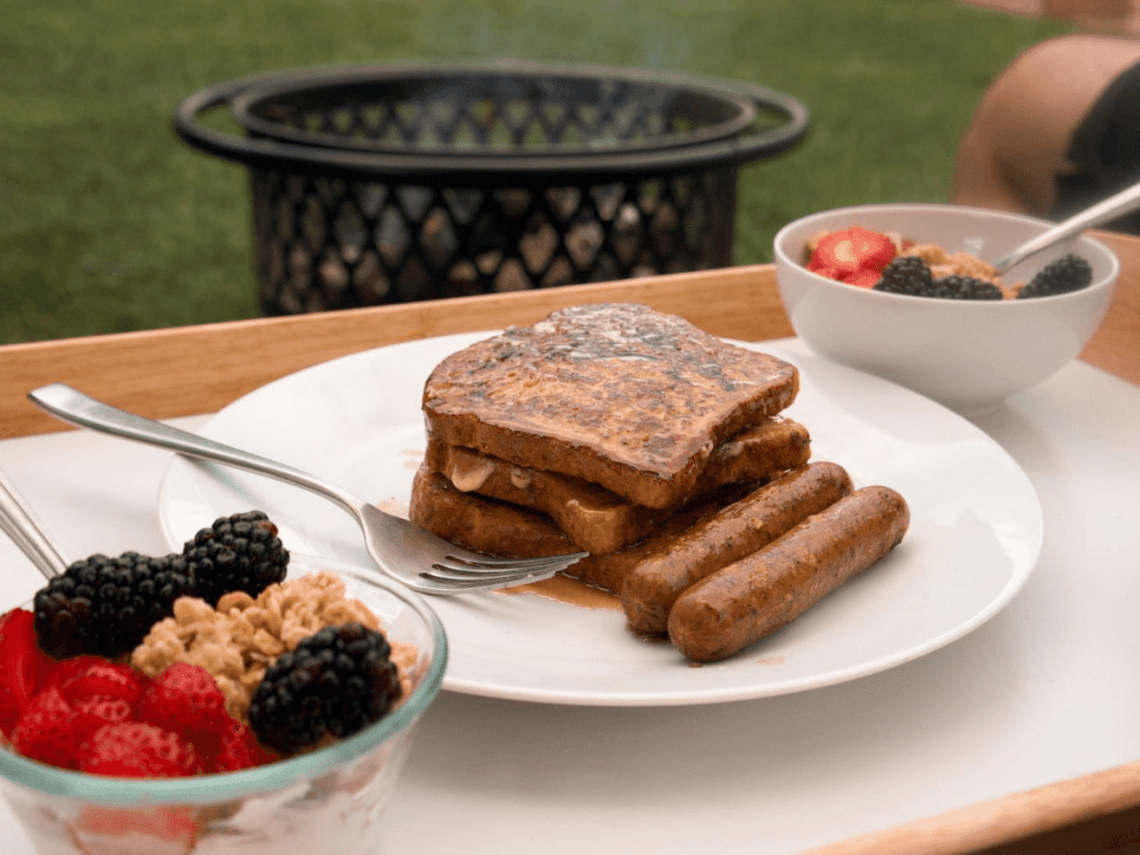 plate with french toast and breakfast sausage plus bowls of yogurt, berries, and granola, breakfast ideas while backyad camping
