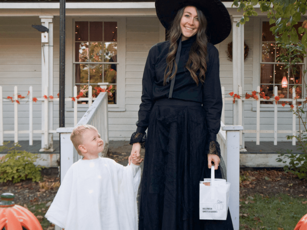 fall bucket list, small boy dressed as ghost holding mom's hand while trick-or-treating