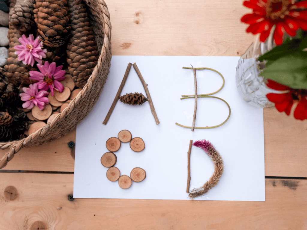 preschool activities, letters a, b, c, and d created on a piece of paper using twigs, pine cones, and wood slices.