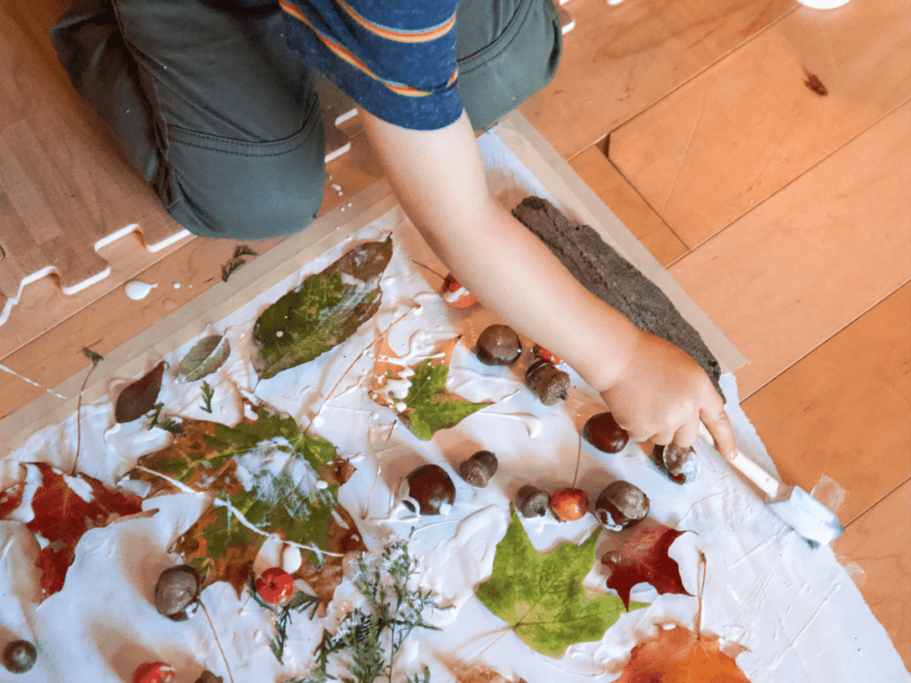 fall crafts for kids; close up of kid's hand gluing leaves onto paper