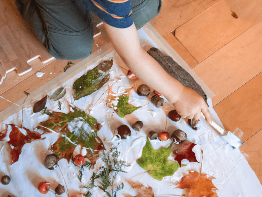 fall bucket list, boy's hand gluing fall leaves onto paper to make autumn nature collage