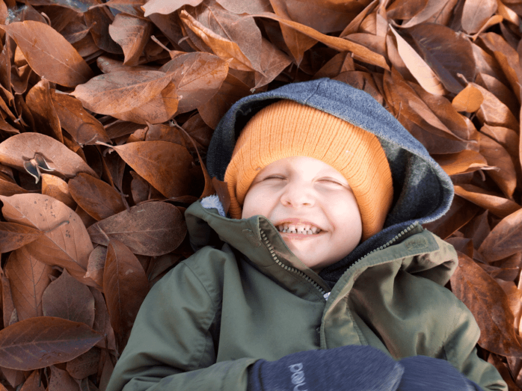 fall bucket list, small boy laying in pile of leaves and laughing