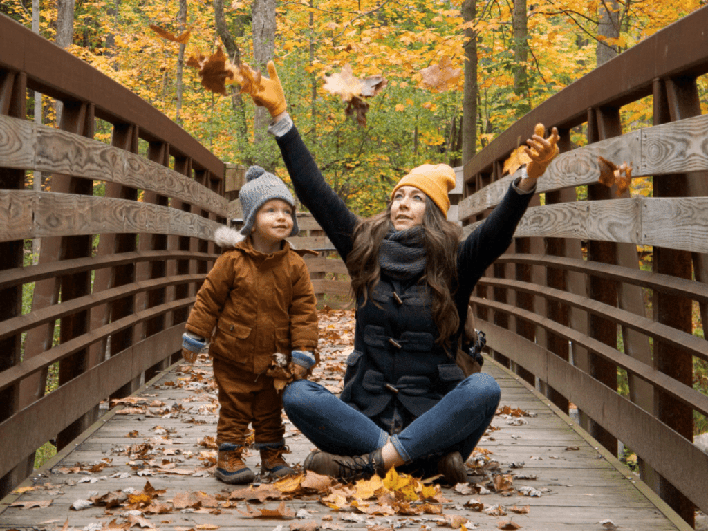 fall bucket list, small boy and his mom on bridge throwing colorful leaves in the air