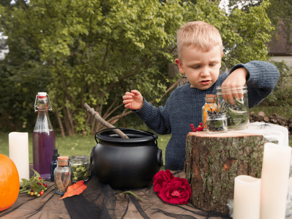 halloween activities for kids, young boy at table with cauldron and bottles of ingredients for potion mixing