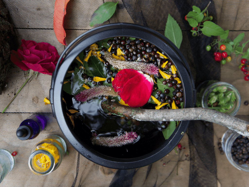 halloween activities for kids, close up of cauldron filled with flower petals, berries, and leaves