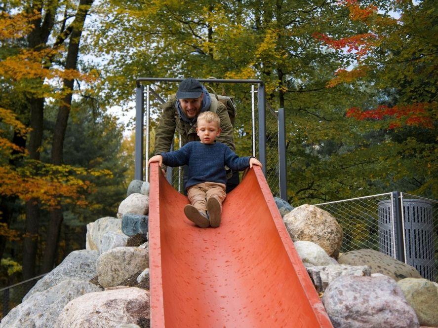 small boy on top of slide at dow gardens playground