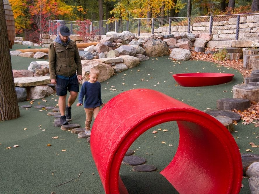 small boy and father walking on tree stumps toward large red tunnel on playground at dow gardens