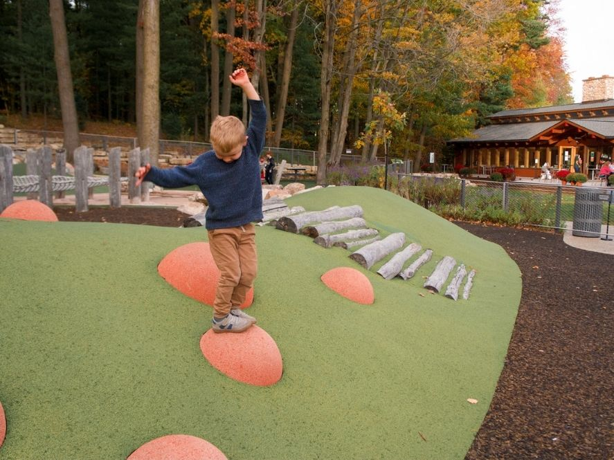 small boy balancing on ball at playground in dow gardens