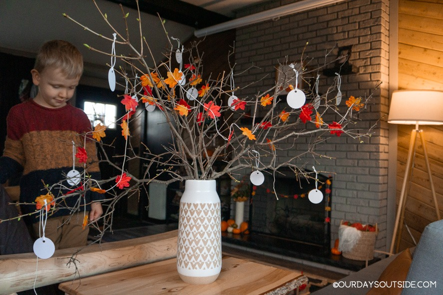 several branches in a vase decorated with leaves as a thankful tree
