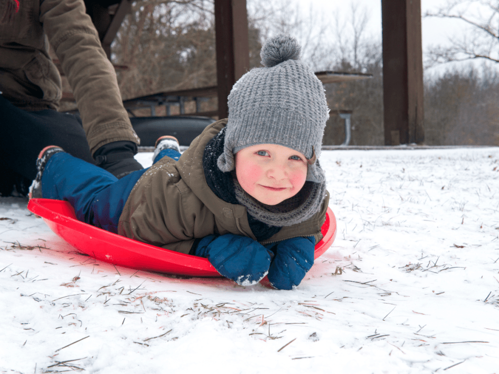 small boy laying on sled