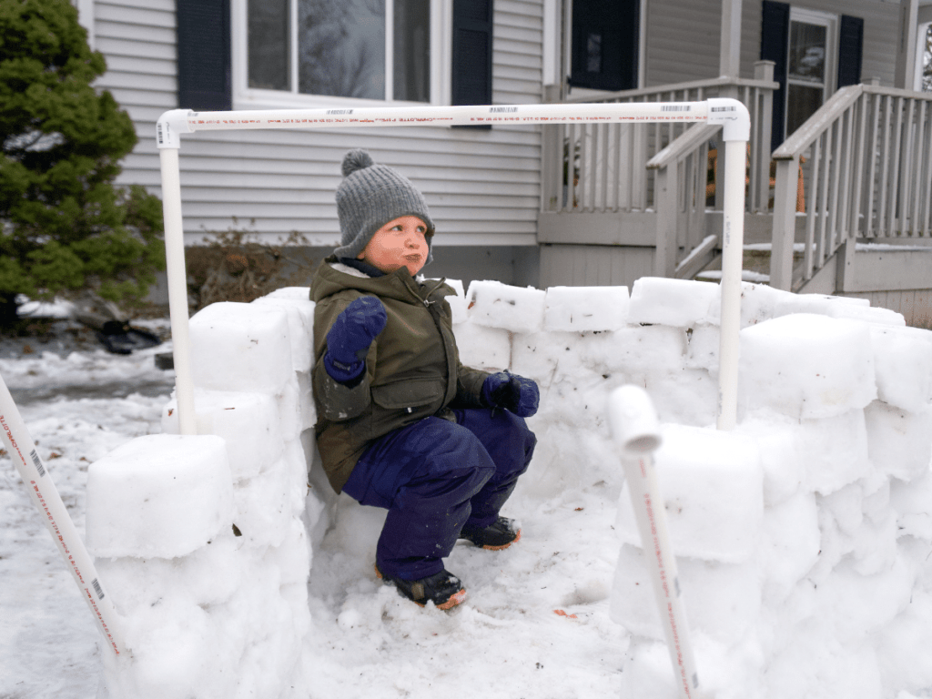 small boy sitting in snow fort