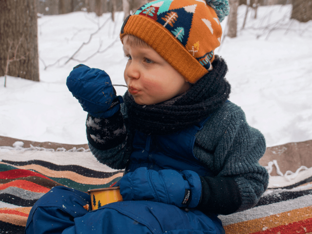 small boy eating chili outside on blanket