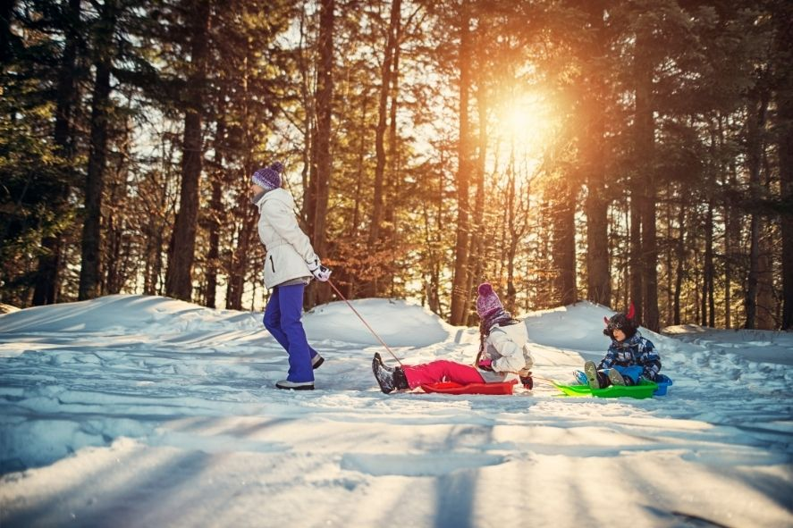 Mom pulling two kids on sleds through the woods while winter hiking with kids