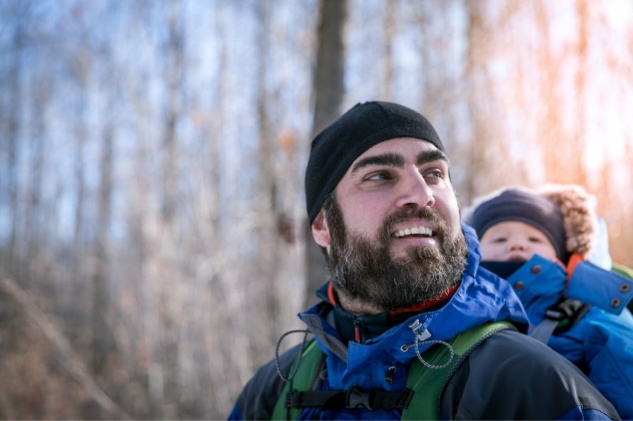 Father carrying baby on his back while hiking