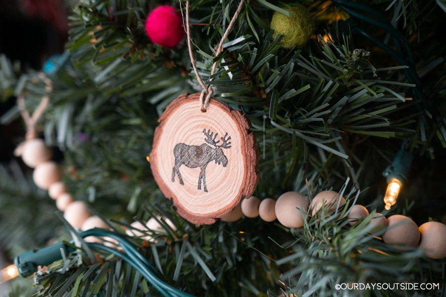 wood slab ornament with moose hanging on christmas tree