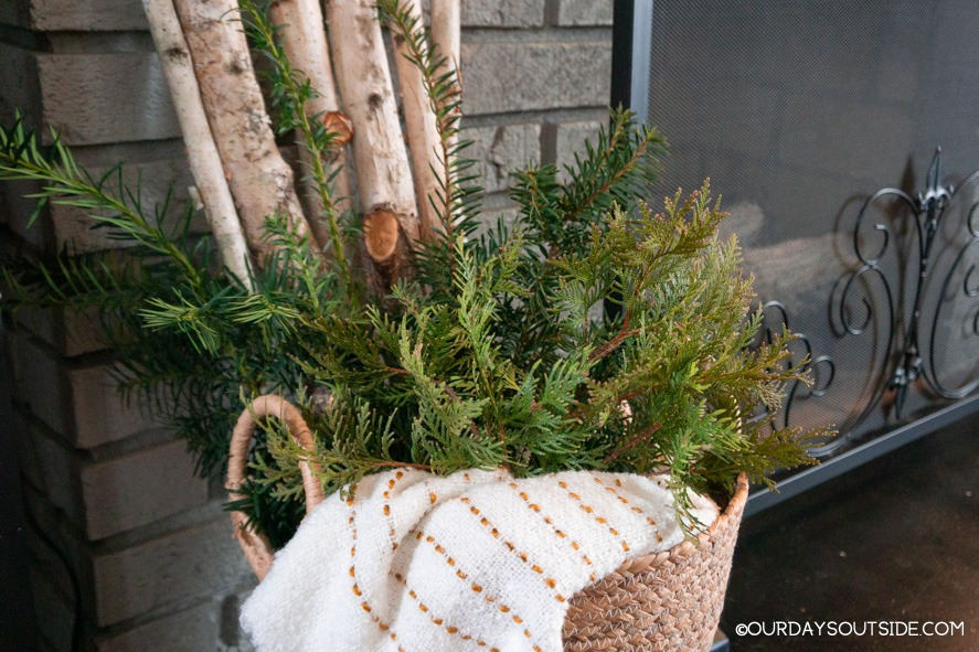 basket with birch logs and greenery next to fireplace