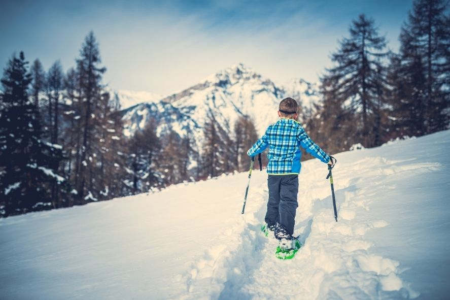 boy snowshoeing on a trail