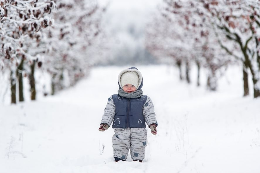 toddler outside in snow wearing puffy snowsuit
