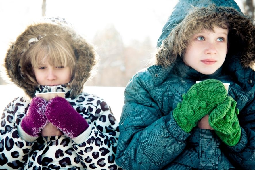 kids sipping hot drinks outside in snow