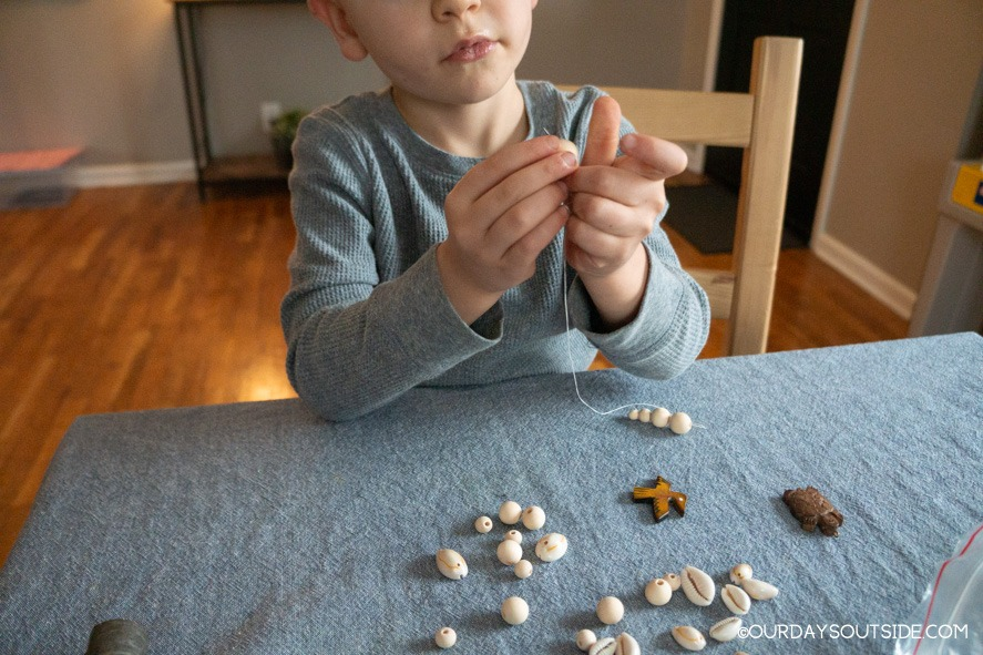 boy stringing beads for diy walking stick