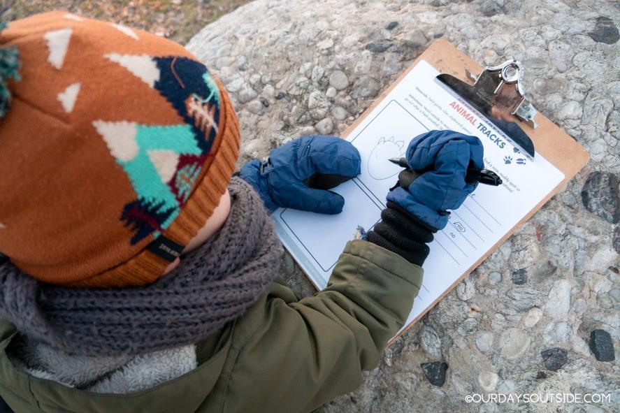 small boy writing on clipboard