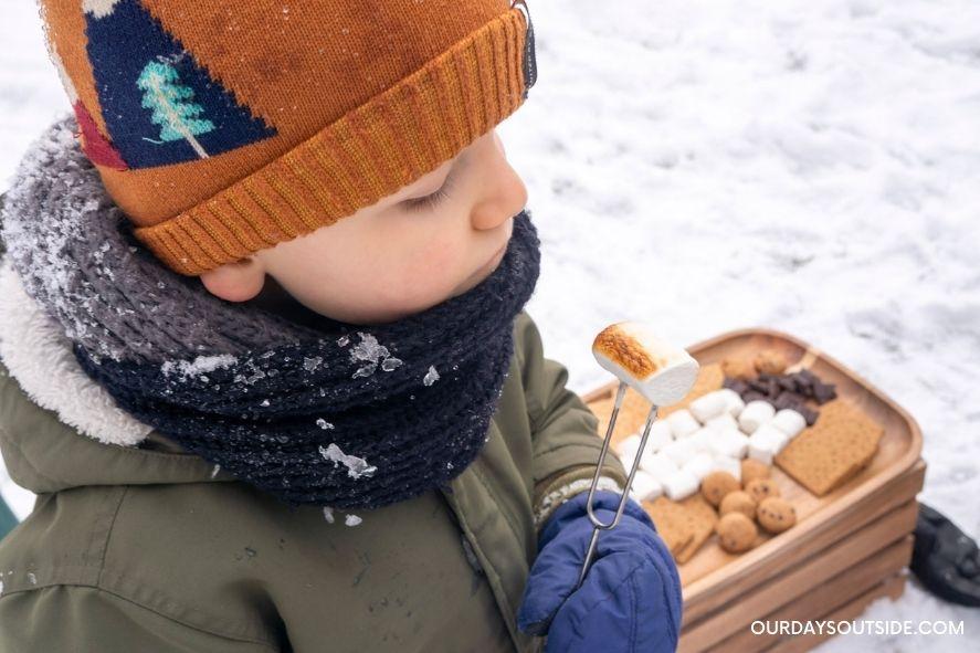 boy holding up roasted marshmallow