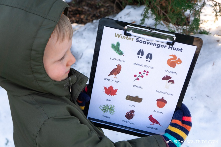 small boy holding winter printable with nature scavenger hunt