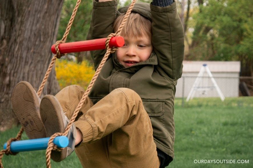 Young boy swinging from rope ladder in tree- improved gross motor skills are one of the benefits of outdoor play